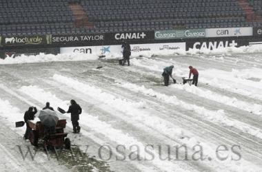 Los operarios de Osasuna trabajan para retirar la nieve del terreno de juego.