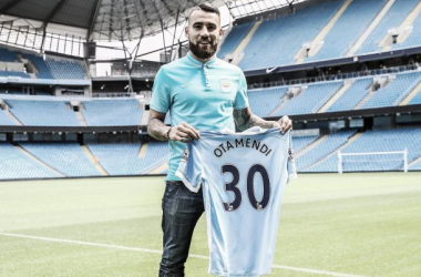 City's new signing unveiled at the Etihad, holding his new shirt.