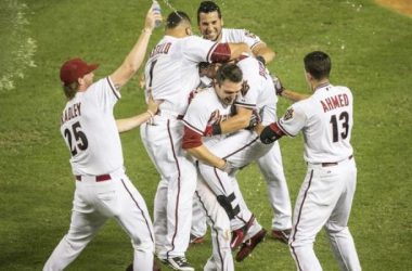 Cliff Pennington is mobbed by teammates after his walk-off sacrifice fly in the 10th. Azcentral sports/Patrick Breen