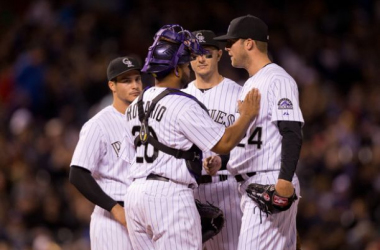 Starting pitcher Jordan Lyles #24 of the Colorado Rockies is congratulated on a solid outing of seven innings pitched by teammates Wilin Rosario #20, Nolan Arenado #28 and Troy Tulowitzki #2 before being removed from the game during the eighth inning agai