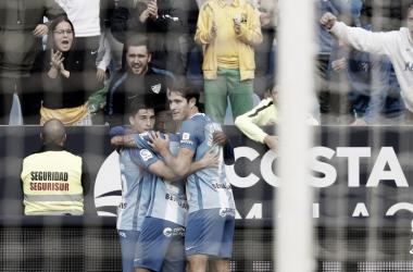 Jugadores malaguistas celebran un gol junto a sus aficionados <vía LaLiga.es>
