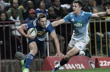 Foto: SP Marais, fullback de Stormers, intenta evadir a Matt Duffie, wing de Blues. En Sudáfrica, los pupilos de Robbie Fleck retornaron a la senda del triunfo. (Sydney Morning Herald).