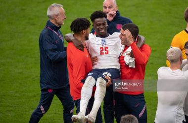 LONDON, ENGLAND - JULY 07: Tyrone Mings and Conor Coady of England pick up team mate Bukayo Saka after the UEFA Euro 2020 Championship Semi-final match between England and Denmark at Wembley Stadium on July 07, 2021 in London, England. (Photo by Visionhausl/Getty Images)