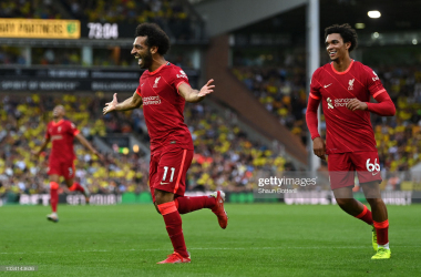 NORWICH, ENGLAND - AUGUST 14: Mohamed Salah of Liverpool celebrates with teammate Trent Alexander-Arnold (L) after scoring their side's third goal during the Premier League match between Norwich City and Liverpool at Carrow Road on August 14, 2021 in Norwich, England. (Photo by Shaun Botterill/Getty Images)