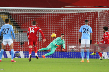 LIVERPOOL, ENGLAND - FEBRUARY 07: Mohamed Salah of Liverpool scores their side's first goal past Ederson of Manchester City from the penalty spot during the Premier League match between Liverpool and Manchester City at Anfield on February 07, 2021 in Liverpool, England. Sporting stadiums around the UK remain under strict restrictions due to the Coronavirus Pandemic as Government social distancing laws prohibit fans inside venues resulting in games being played behind closed doors. (Photo by Matt McNulty - Manchester City/Manchester City FC via Getty Images)
