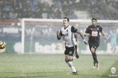 Santi Mina corriendo tras el esférico bajo la lluvia en Ipurua. Fuente: Valencia CF.