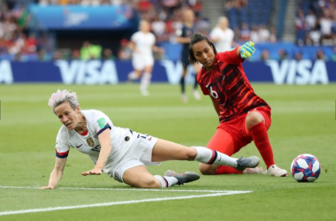 Megan Rapinoe (left) is challenged outside of the box by France goalkeeper Sarah Bouhaddi (right). | Photo:Elsa Garrison - Getty