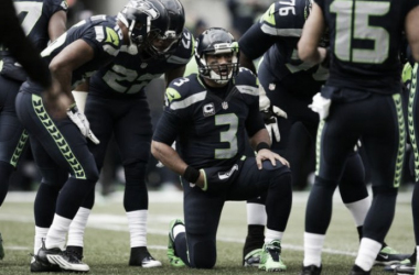 Seattle Seahawks quarterback Russell Wilson kneels in the huddle to read out a play to the offense in a game. Image via AP.