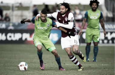 Seattle Sounders right back Tyrone Mears (left, in green) tries to dribble away from Colorado Rapids midfielder Jermaine Jones (right, in brown, #13) during the Sounders' 1-0 win over the Rapids on Sunday. Photo credit: Daniel Petty/The Denver P