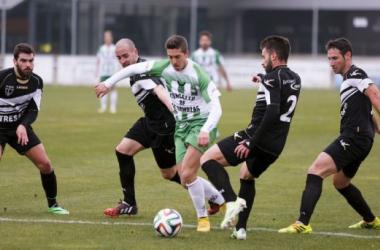 Un jugador del Somozas trata de superar a varios defensores negrillos. (Foto: César Toimil, www.lavozdegalicia.es)