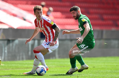 STOKE ON TRENT, ENGLAND - APRIL 17: Josh Tymon of Stoke City battles for possession with Ched Evans of Preston North End during the Sky Bet Championship match between Stoke City and Preston North End at Bet365 Stadium on April 17, 2021 in Stoke on Trent, England. Sporting stadiums around the UK remain under strict restrictions due to the Coronavirus Pandemic as Government social distancing laws prohibit fans inside venues resulting in games being played behind closed doors. (Photo by Gareth Copley/Getty Images)
