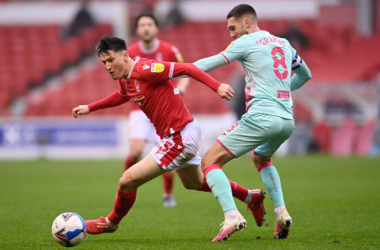 Joe Lolley of Nottingham Forest breaks past Matt Grimes of Swansea City during the Sky Bet Championship match between Nottingham Forest and Huddersfield Town at City Ground on November 29, 2020, in Nottingham, England. Sporting stadiums around the UK remain under strict restrictions due to the Coronavirus Pandemic as Government social distancing laws prohibit fans inside venues resulting in games being played behind closed doors. (Photo by Laurence Griffiths/Getty Images)