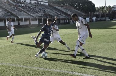 Marcos Figueroa con los pies en la pelota mientras es acorralado por dos jugadores rivales. Foto: Prensa Temperley