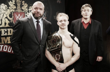 Tyler Bate celebrates his championship win with Triple H and William Regal. Photo: WWE.com