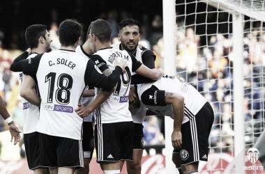 La piña de jugadores che celebrando los goles ante el Alavés. Fuente: Valencia CF.