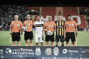 Rinaudo, capitán de GELP. Ruben, capitán de CARC. Ambos posan junto a la terna arbitral a minutos de comenzar la final. Foto: @Copa_Argentina en Twitter.