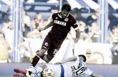 Gastón Giménez yendo a buscar la pelota al piso, trabando con Facundo Quignón, volante de Lanús. | Fuente: Lanús.
