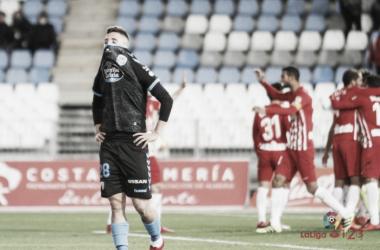 Escriche lamentándose del resultado del partido mientras los jugadores del Almería celebran al fondo | LaLiga.es