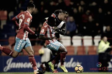 Leuko y De Tomás pugnan por el balón ante la mirada de Luís Muñoz | Foto: LaLiga