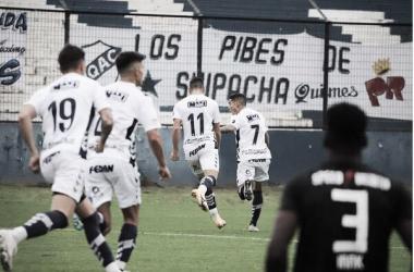 Bonetto celebrando el 1-1 con sus compañeros (blancos) y Murillo frustrado en el piso (negro) (Fuente: Prensa Quilmes).