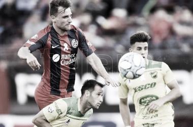 Bruno Pittón (rojo) disputando la pelota contra un rival. Fuente: Web.