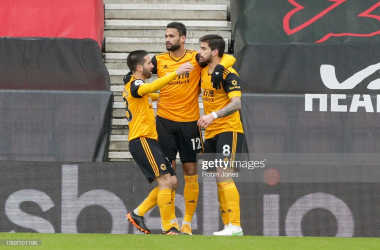 SOUTHAMPTON, ENGLAND - FEBRUARY 14: Ruben Neves of Wolverhampton Wanderers celebrates with team-mates Joao Moutinho and Willian Jose after he scores a goal to make it 1-1 from the spot after a penalty is awarded against Ryan Bertrand of Southampton for handball during the Premier League match between Southampton and Wolverhampton Wanderers at St Mary's Stadium on February 14, 2021 in Southampton, England. Sporting stadiums around the UK remain under strict restrictions due to the Coronavirus Pandemic as Government social distancing laws prohibit fans inside venues resulting in games being played behind closed doors. (Photo by Robin Jones/Getty Images)