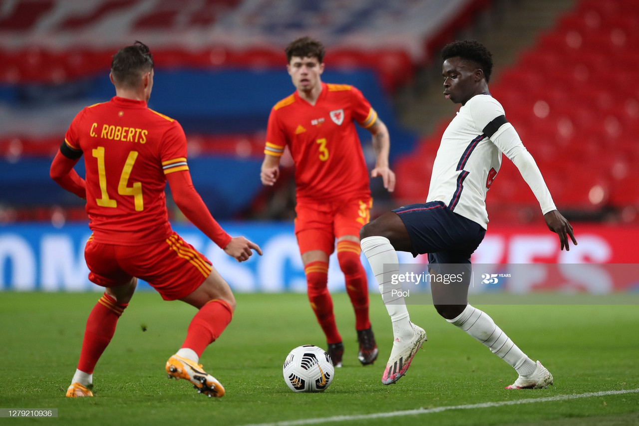 LONDON, ENGLAND - OCTOBER 08: Connor Roberts of Wales looks on as Bukayo Saka of England controls the ball during the international friendly match between England and Wales at Wembley Stadium on October 08, 2020 in London, England. Sporting stadiums around the UK remain under strict restrictions due to the Coronavirus Pandemic as Government social distancing laws prohibit fans inside venues resulting in games being played behind closed doors. (Photo by Nick Potts - Pool/Getty Images)