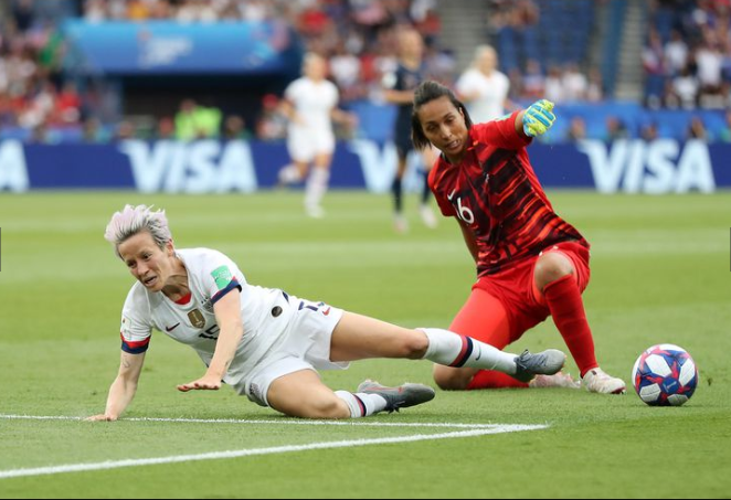 Megan Rapinoe (left) is challenged outside of the box by France goalkeeper Sarah Bouhaddi (right). | Photo:Elsa Garrison - Getty