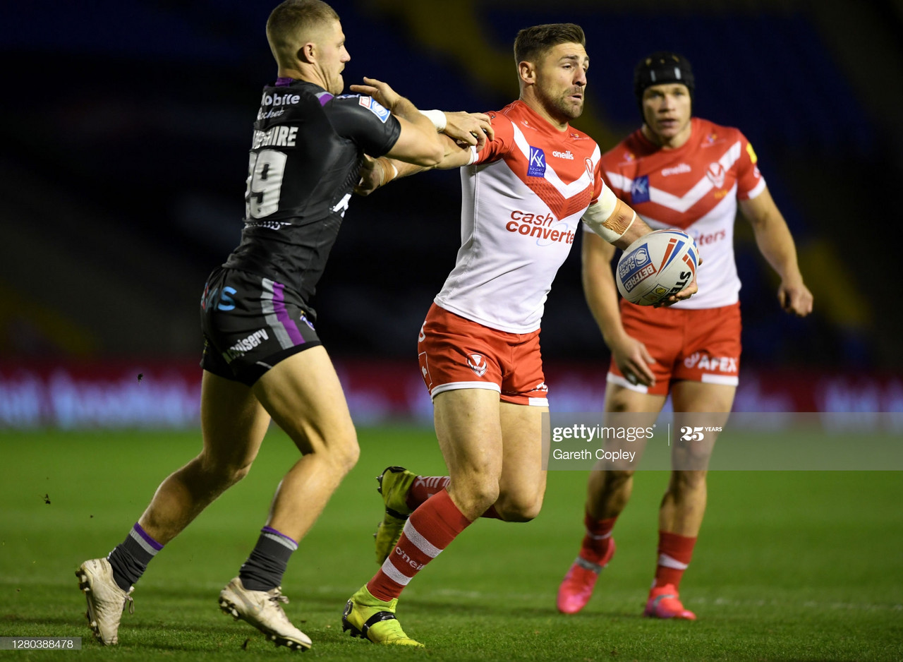 WARRINGTON, ENGLAND - OCTOBER 15: Tommy Makinson of St Helens is tackled by Ryan Hampshire of Wakefield during the Betfred Super League match between St Helens and Wakefield Trinity at The Halliwell Jones Stadium on October 15, 2020 in Warrington, England.Sporting stadiums around the UK remain under strict restrictions due to the Coronavirus Pandemic as Government social distancing laws prohibit fans inside venues resulting in games being played behind closed doors. (Photo by Gareth Copley/Getty Images)